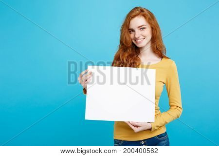 Business Concept -Close up Portrait young beautiful attractive ginger red hair girl smiling showing blank sign. Blue Pastel Background. Copy space.