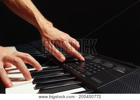 Hands of pianist play the keys of the electronic synthesizer on a black background