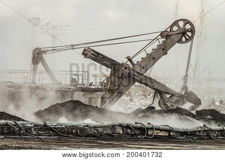 large bucket excavator works in a hot outdoors dump. Heavy industrial metallurgical foggy landscape