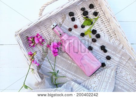 smoothie of blackberries in the bottle with fresh berries and flowers