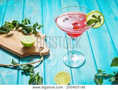 Coctail margarita with lime on blue wood background.