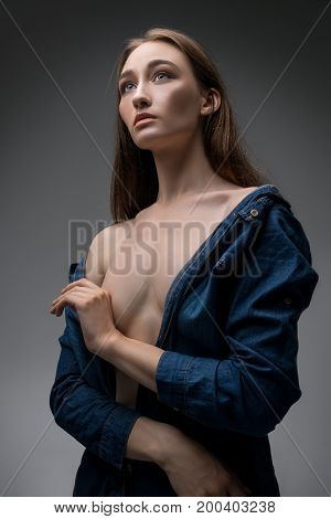 Beautiful sexy blonde wearing jeans unbuttoned shirt posing against gray wall