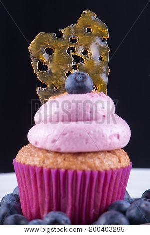 Detail of cannabis oil concentrate aka shatter against over a pink cupcake with blue berries