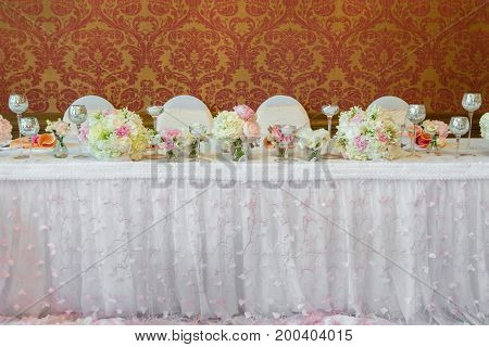Decoration of the table in a pink style. Wedding decorations in pink tones. Glasses and plates on the layer.