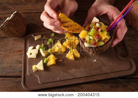 Decoration of tropical fruit salad in coconut shell. Apple, orange, kiwifruit and pomegranate ingredients are mixed in nut bowl with straws