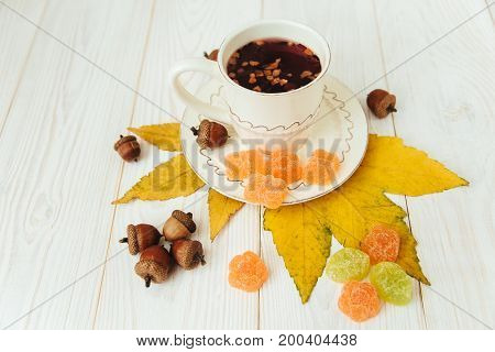 Cup of fruit tee with autumn elements on the white wood.Jelly candyleavesacorns.