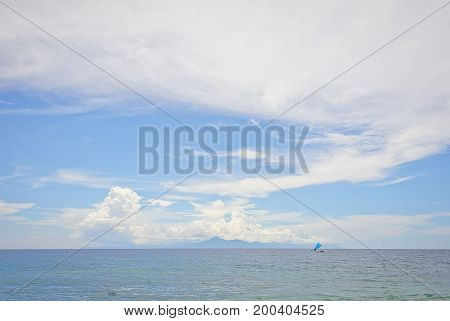 Fishing boat under a blue sail in a calm ocean against a background of an island with mountains and blue sky. Journey to a tropical island. Calm and new impressions.