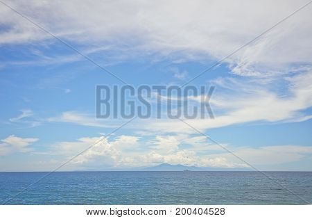 Calm ocean during a hot summer day on a tropical island. A wide view of the island of Bali and the Agung volcano on the horizon from the island of Lombok in Indonesia. Travel to a tropical island, tranquility and serenity.
