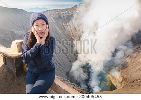 Portrait of beautiful asian woman smiles happily and sitting on volcano crater with erupting smoke located in Bromo Tengger Semeru National Park East Java Indonesia. The weather is cold.