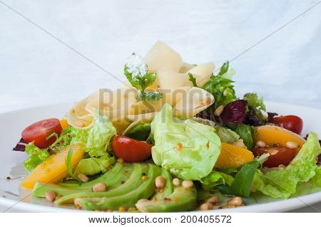 Tasty green salad with cheese and fruits on plate. Lettuce, fresh vegetables decorated pine nuts, avocado and pearch, serving in restaurant, close up picture