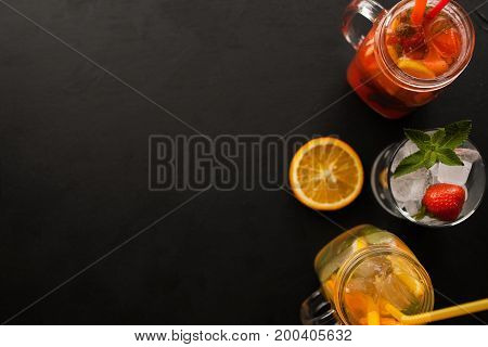 Top view fresh cocktails on black background. Orange and strawberry cold drink in jar and glass with ice decorated mint and sliced citrus, refreshment in hot weather free space nearby