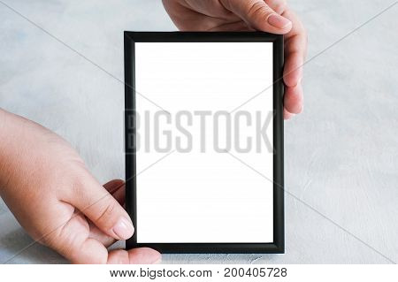 Picture frame tenderly holding in hands. Greetings, concept of tendance and family memories, close up with copy space