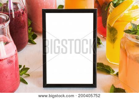 Blank picture frame with fresh fruit drinks around. Food blogs, menu and recipes for web sites of cafe and restaurant, close up picture with copy space