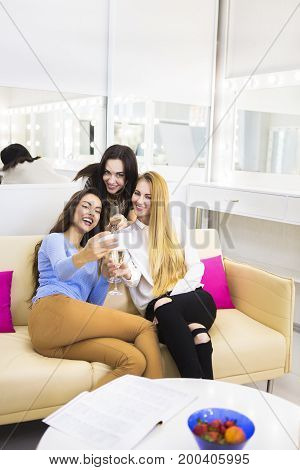 Three young pretty woman having fun drinking champagne and making selfie. Celebration and lifestyle concept
