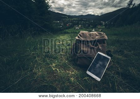 beautiful landscape of the mountians with dramatic clouds with backpack and mobile phone near it