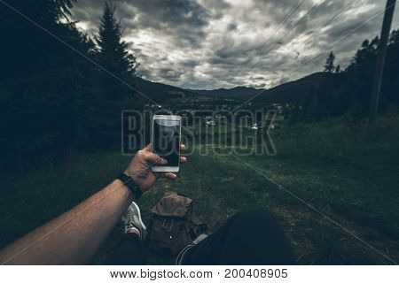 man lying on the ground and taking picture of summer mountains