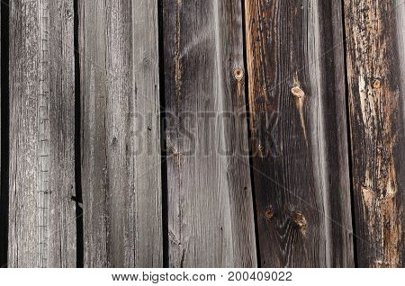 Texture dark wooden boards with brown and gray spots. With holes on the boards. Horizontal photo wallpaper