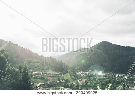 beautiful landscape on the village in mountains with rain, clouds