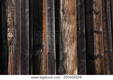 Texture new dark wooden boards with brown spots and bulges. Horizontal photo wallpaper