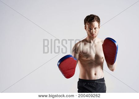 Martial arts kickboxing sports fitness and active lifestyle concept. Professional bearded boxer or trainer with tattoo sport mitts in gym training having serious determined expression on his face