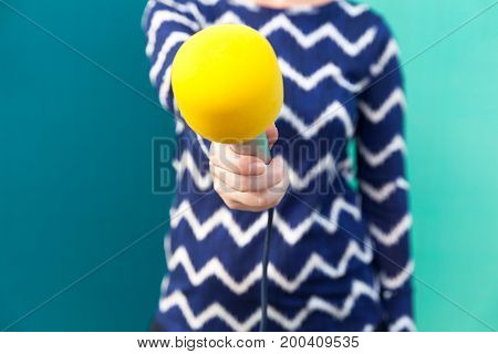 Female journalist holding microphone at press conference