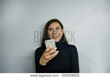 Cheerful young female with long dark hair and braces holding generic smart phone grinning broadly typing sms or browsing newsfeed via social networks enjoying online communication at home