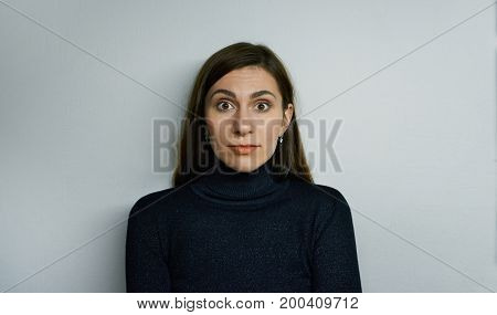 Picture of funny emotional bug-eyed brunette girl of European appearance looking at camera having shocked amazed expression on her pretty face. Human emotions feelings reaction and attitude