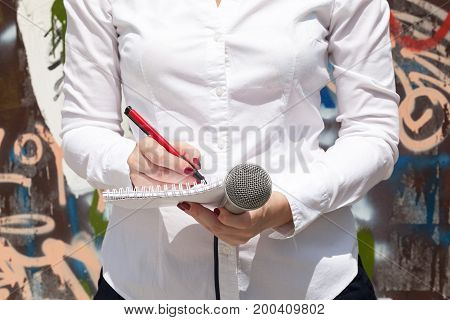 Female reporter at press event taking notes, holding microphone