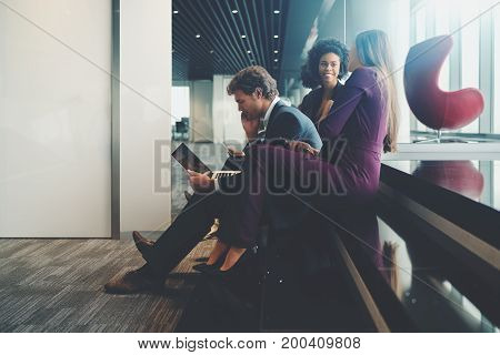 Two young businesswomen of different races having funny conversation behind the back of their boss which is working with laptop while all three together sitting on step of office stairway near windows