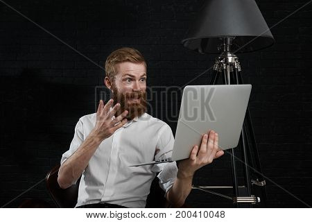 Picture of excited young red-haired male photographer with fuzzy beard dressed in white shirt holding open laptop in front of him and gesturing while making video call using online services