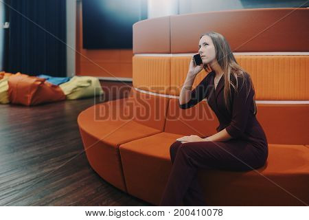 Thoughtful caucasian businesswoman is sitting on round sofa in chill out area of modern office and having phone conversation with copy space zone for message text or advert