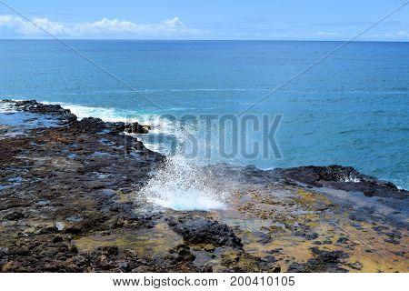 Waves crashing onto volcanic lava rocks taken at tide pools taken in Kauai, HI