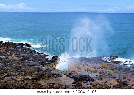 Waves crashing onto the rural rugged Hawaiian Coast with volcanic lava rocks taken in Kauai, HI