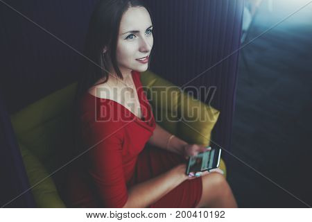 Charming caucasian business lady in red dress is sitting on fenced office armchair holding smartphone and thoughtfully looking somewhere aside