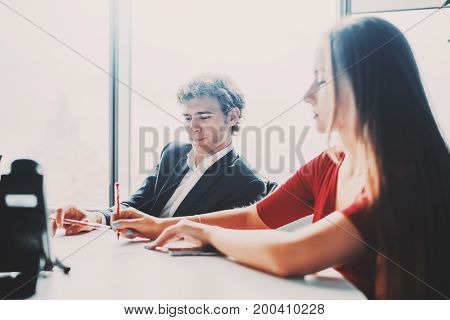 Business meeting in office next to window of man employer and his female colleague in foreground in red dress with long hair she is using sheet of paper and pen to explain develop plan to her boss