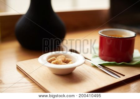 Detailed close up shot of red mug of coffee or tea bowl with brown sugar cubes and cutlery on wooden tray on cafe table by the window. Drinks food leisure and beverage concept. Selective focus