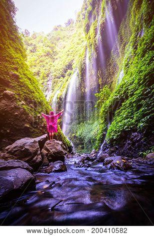 Happy Man standing on the rock in Madakaripura Waterfall Java Indonesia. Travel concept and discovery