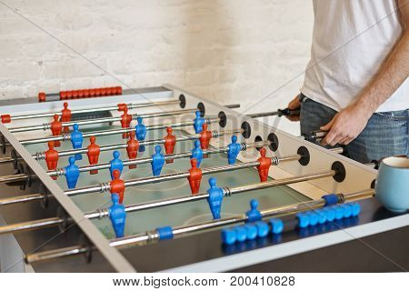 Cropped shot of unreconizable man in white t-shirt and jeans playing foosball in bar controling blue foos men. Close up view of male hands moving rods to play defense during table football match