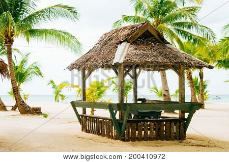 Landscape of paradise tropical island with palms cottages and white sand beach