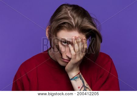 Disappointment in yourself. Young male misfortune. Disaster in relationship, modern youth concept. Upset guy on blue background