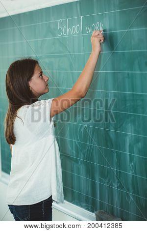 Happy schoolchild writing on blackboard in classroom