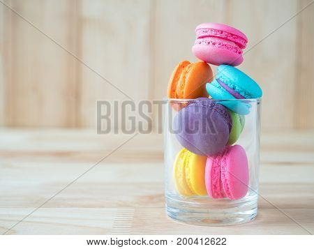 Closeup stack of colorful macaroons on glass with copy space on wood background