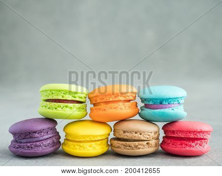 Closeup assortment of colorful Macaroons with copy space on bare cement or concrete wall background