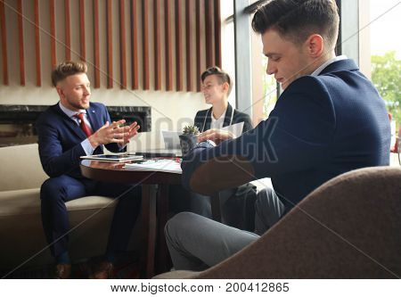 Businessman looks at his wrist watch checking the time. Businessperson sitting a meeting and working at background