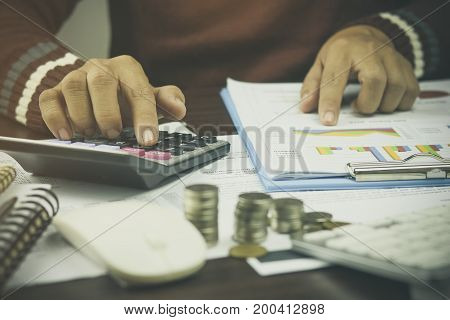 Hand of businessman writing pile coin money with account book finance and banking for background.concept in grow and walk step by step for success in business