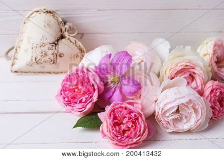 Sweet pastel roses clematis flower and decorative heart on white wooden background. Selective focus is on flowers.