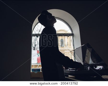 Male enjoys listening to music on vinyl records. Special dark atmospheric interior, creative musical shop, unrecognizable listener