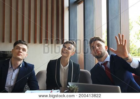 Portrait of three partners discussing ideas at meeting