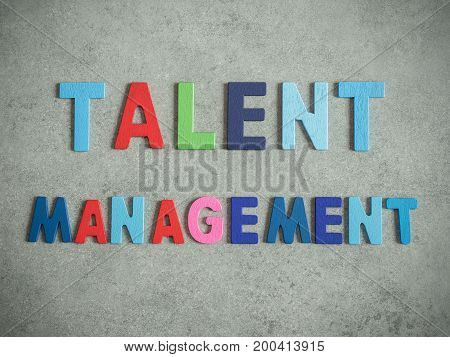 Word spell Talent Management on bare cement or concrete wall background