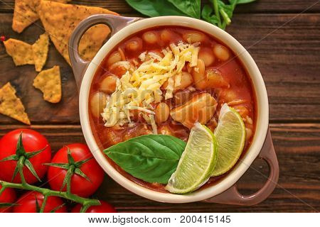 Composition with delicious turkey chili in casserole on wooden table